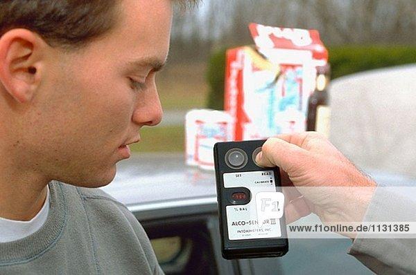 Polizist zeigt Alkohol Atem Testergebnisse zu Teen Stecker