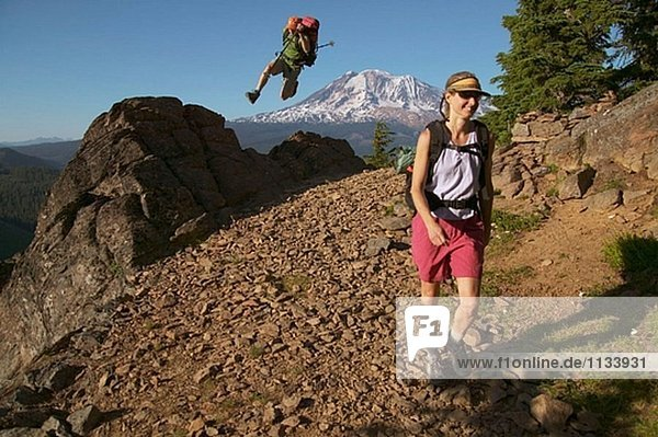 Ein Mann springt aus einem Felsen beim Wandern auf einem Pfad in der Nähe von Mount Adams. Washington. USA