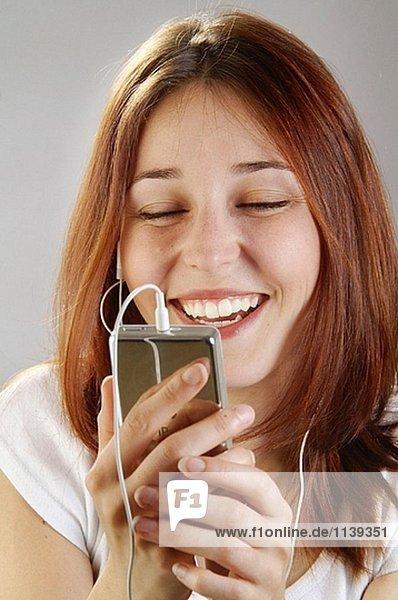 Junge Frau  25  beim hören zu ihrem Ipod lachen