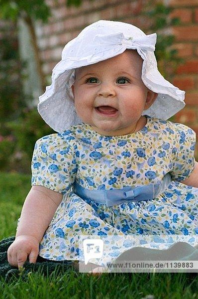 Baby sitting on grass.