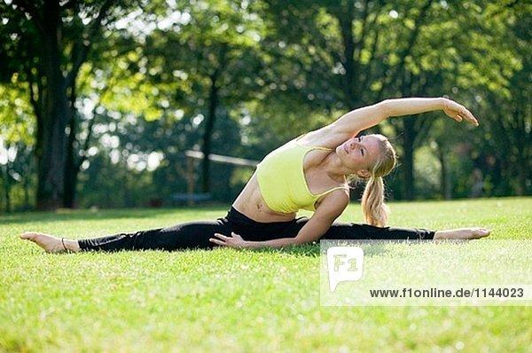 Young Frau macht Gymnastik im park