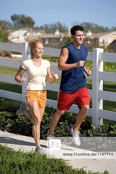 Young couple jogging in front of a white fence