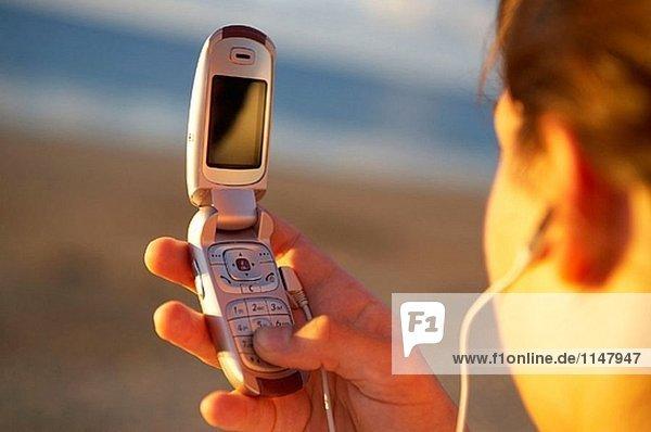 16 Jahre alt Teenager Musikhören in einem MP3-Mobiltelefon. Hendaye Strand. Aquitaine. Frankreich.