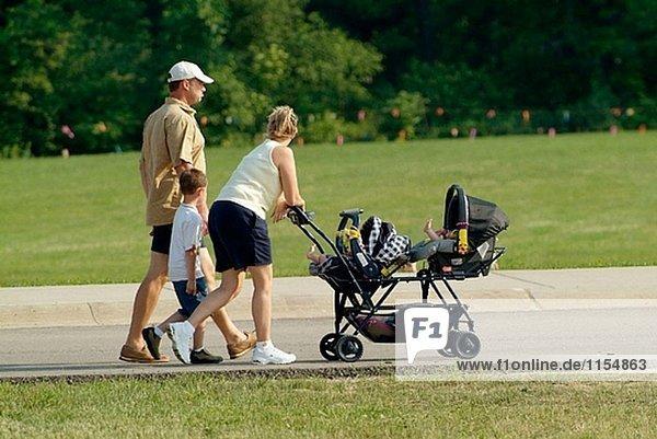 Familie geht zusammen auf dem Bürgersteig während des Besuchs einer Karneval-festival