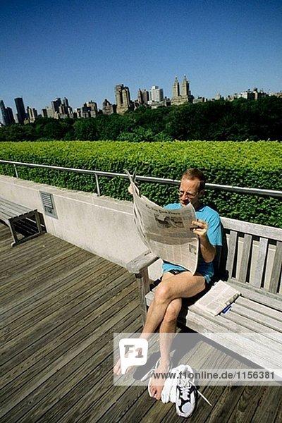 Mann lesen Zeitung im Central Park in New York City. USA