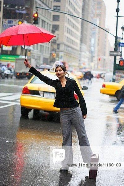 Indische geschäftsfrau mit Regenschirm in New York City im Regen Meldepflicht ein Taxi