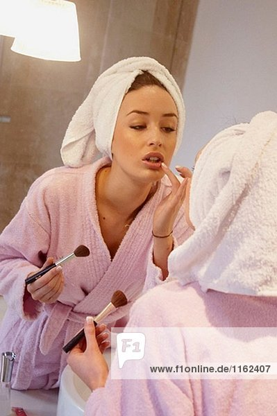 Girl in robe applying make up at the bathroom mirror