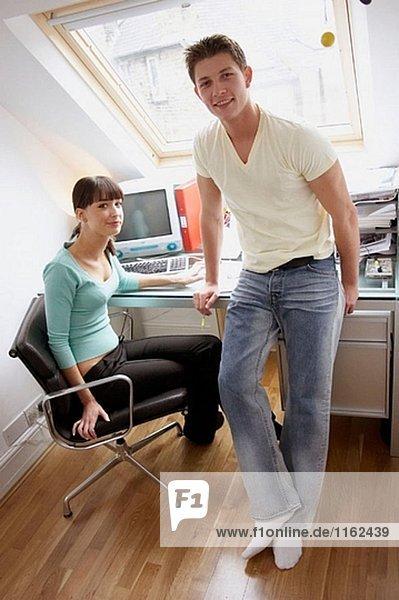 junges Paar zusammen im Büro Blick in die Kamera  lächelnd.