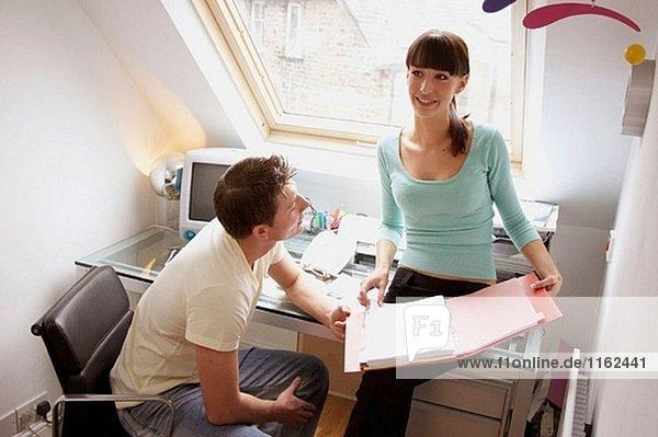 junges Paar zusammen im Blick auf eine Datei  Büro lächelnd