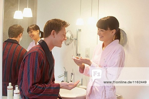 Young couple standing together in bathrobes in the bathroom laughing.