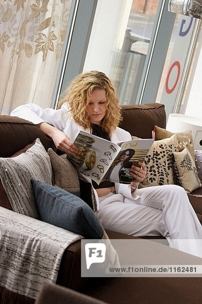 20 year old girl sitting on the sofa reading a book