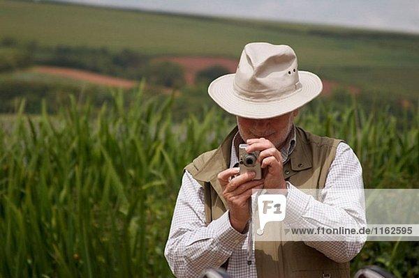 Älterer Mann Aufnahme eines Fotos in einigen Schilf an einem See  Devon  England. UK.