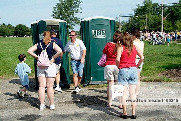 Menschen richten Sie eine öffentliche tragbare Toilette verwenden