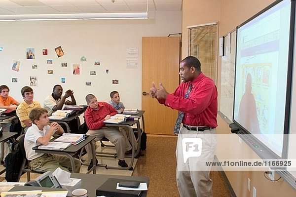 A black instructor teaches French to a class of students using a ´smart board´ or electronic black board.