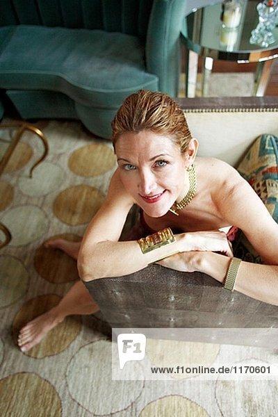 40´s sexy elegante caucasian Lächelnde Frau in der Kamera in ihrem Wohnzimmer