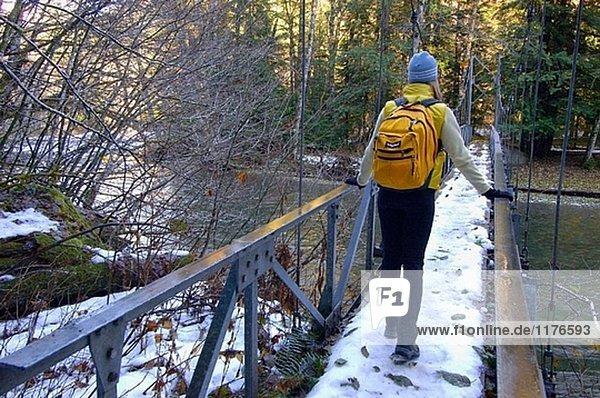Weibliche Wanderer auf Fuß Brücke über Ohanapecosh Fluss Washington USA.