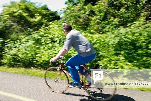 Mittleren Alter Mann fahren Fahrrads auf eine Spur.