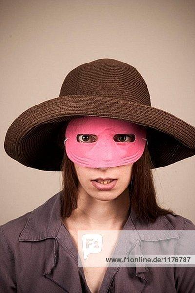 Junge Frau  tragen einen Hut und Pink Mask  posieren