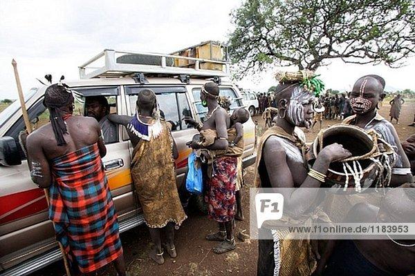Touristen und Mursi Menschen. Omo-Tal Stamm. Süd Äthiopien.