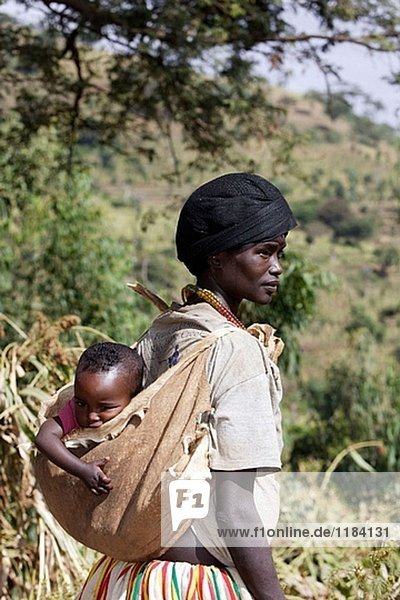 Carrying a baby in a goat skin. To Konso market. Konso Tribe. Ethiopia.