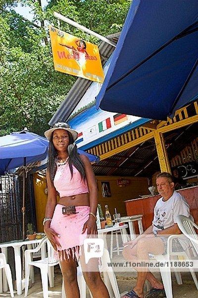 Inhaber Margarita Rodriguez an ihr am Strand Bar  die eiskalten Bier und heissen Frauen wirbt. Sosua  Dominikanische Republik