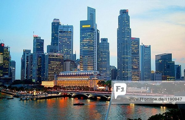 Abend Blick auf die Skyline von Singapur aus Marina Bay  mit Esplanade Brücke  Fullerton Hotel und Merlion. Singapur.