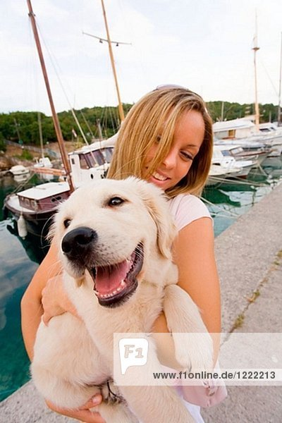 Happy young blond girl is holding her pet dog