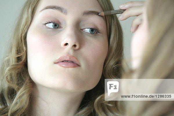 Nahaufnahme of young Frau trägt Augenbrauenstift auf mund