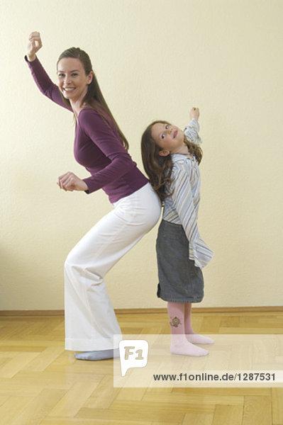 Ganzkörper-Porträt von Mutter und Tochter ständigen Rücken an Rücken Spaß