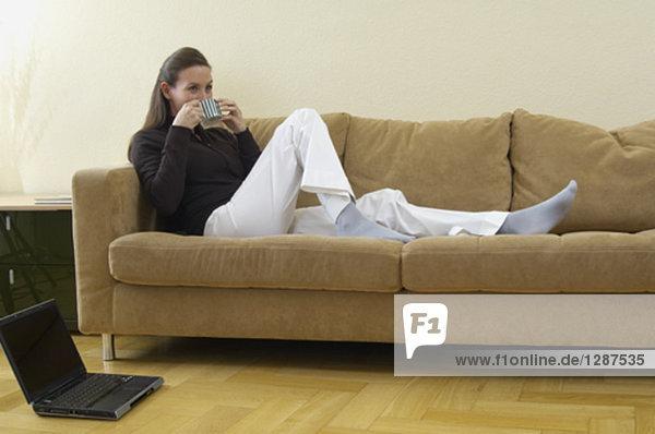 junge Frau auf Sofa mit Tasse Kaffee entspannend