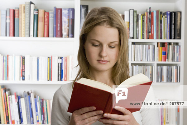 portrait of teenage girl reading book in library