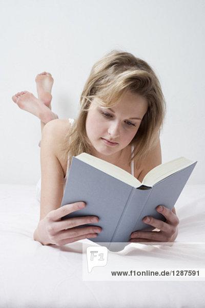 Portrait einer jungen Frau liegend auf Bett Buch zu lesen
