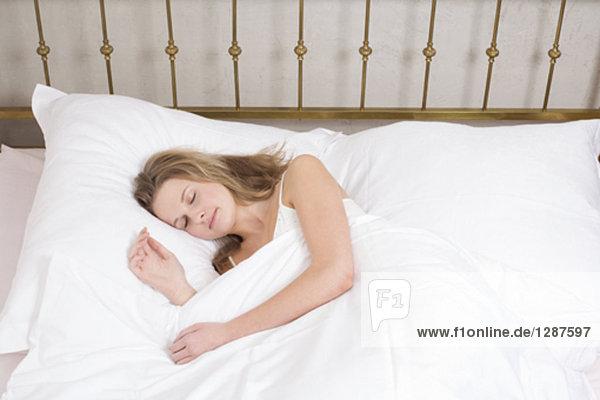 Portrait einer jungen Frau im Bett schlafen