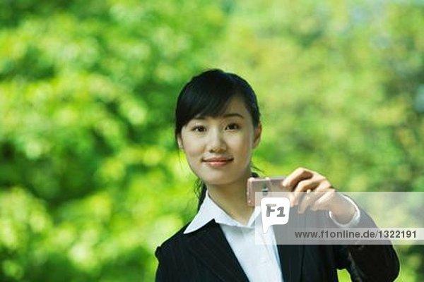 Junge Frau mit Fotophon  lächelnd vor der Kamera