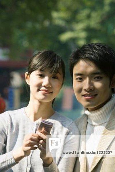 Junges Paar mit Handy  lächelnd in die Kamera  Portrait