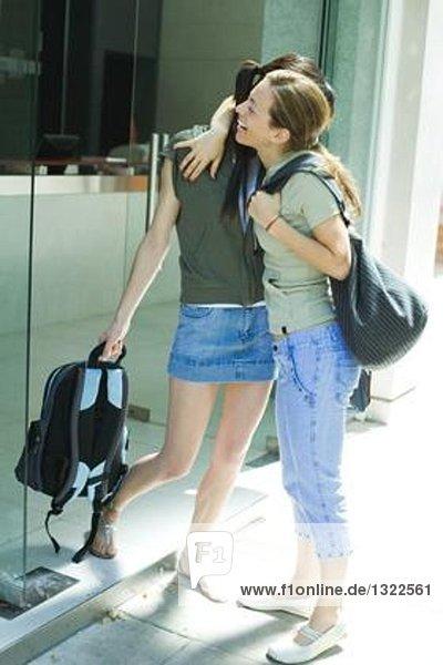 Zwei junge Frauen  die in der Tür stehen und sich umarmen.