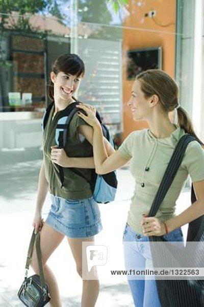 Zwei junge Frauen stehen zusammen auf dem Bürgersteig und lächeln sich an.