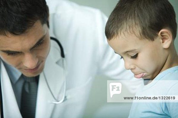 Doctor leaning over boy  boy making face