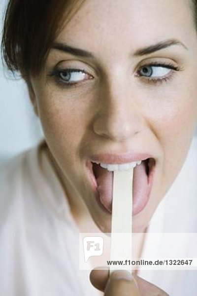 Woman having tongue held down with tongue depressor