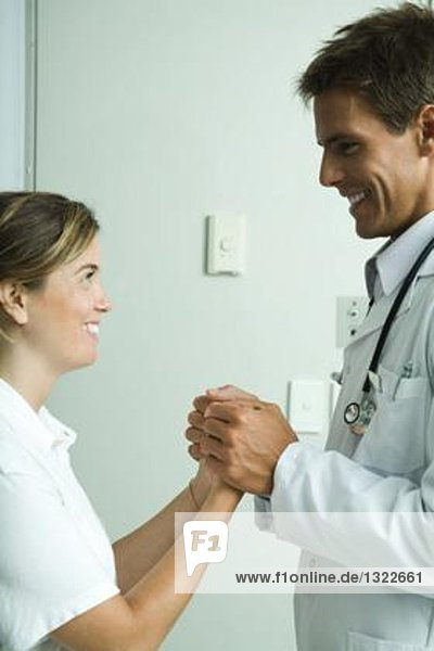 Doctor and woman standing face to face  holding hands and smiling at each other