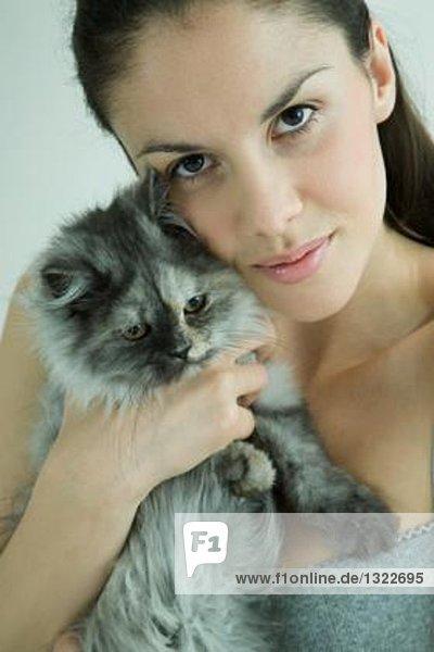 Junge Frau hält Katze an die Wange  lächelt der Kamera entgegen