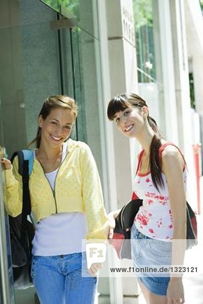 Two young women standing in street clothes  smiling at camera