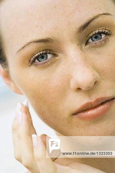 Frau  die Sonnencreme auf das Gesicht aufträgt  Nahaufnahme