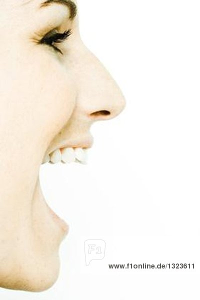 Gesicht einer jungen Frau mit weit geöffnetem Mund  Profil