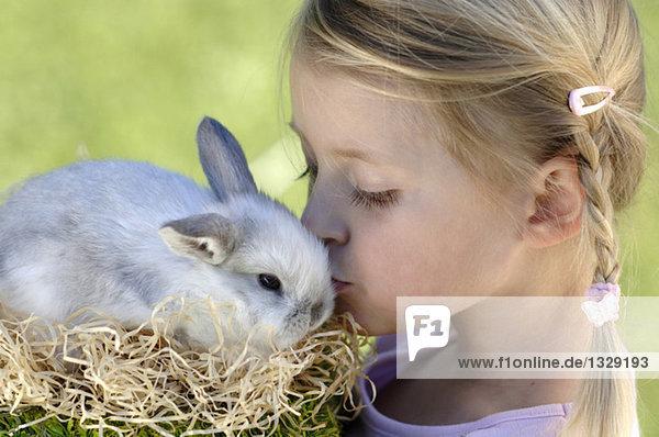 Mädchen (6-7) küssend Osterhase