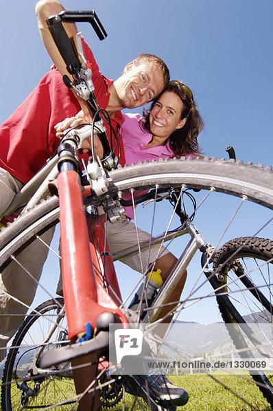 Junges Paar auf dem Fahrrad  lächelnd  Tiefblick  Portrait