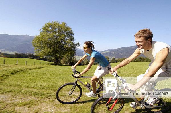 Junges Paar auf dem Mountainbike  lächelnd  Seitenansicht