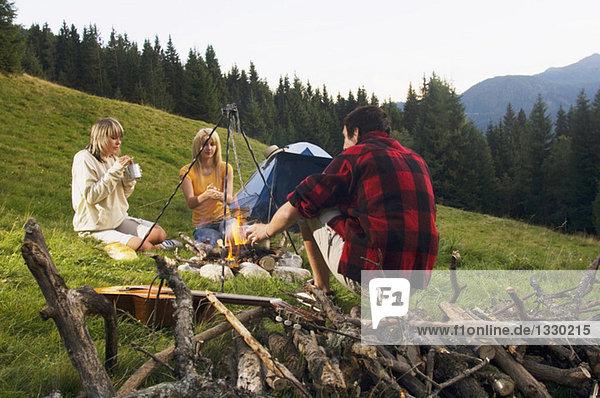 Drei junge Leute  die am Lagerfeuer sitzen.
