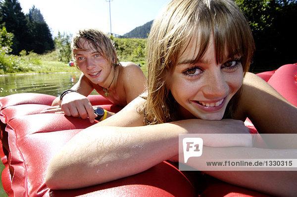 Junges Paar auf Luftbett liegend  lächelnd  Nahaufnahme
