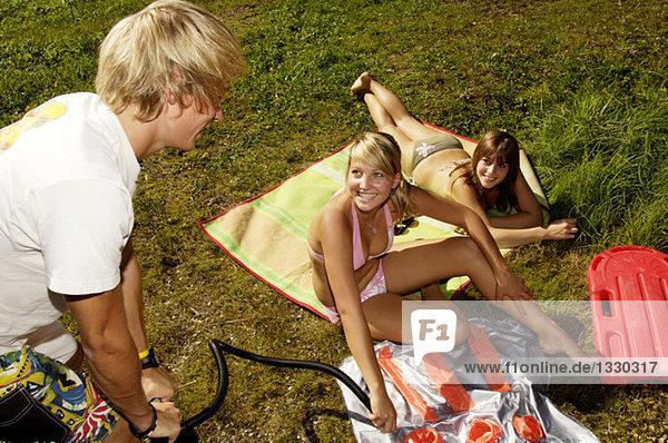 Young man pumping up air mattress  girls watching